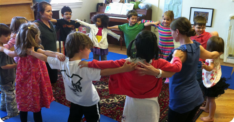 image of an adult interacting with children in the classroomimage of an adults interacting with children in the classroom doing yoga